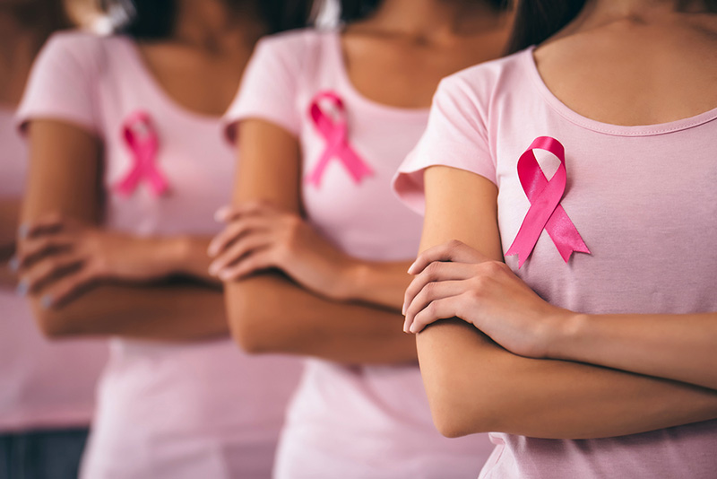 women showcasing a breast cancer ribbon