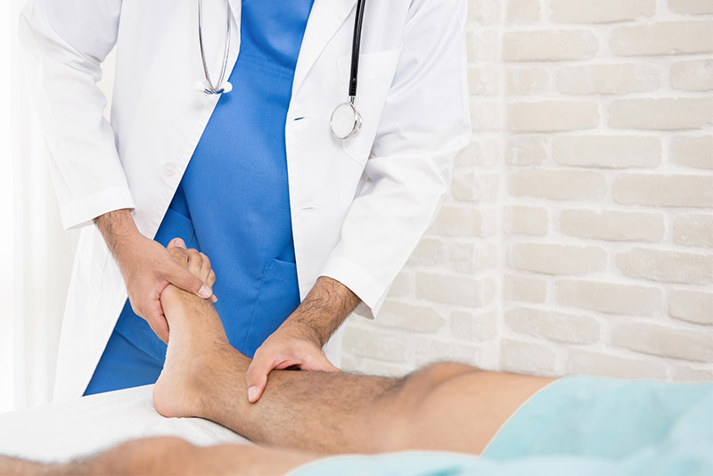 a doctor assesses a patient's leg; how to treat PAD